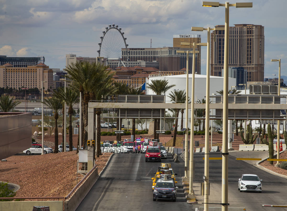 Taxis line up into Terminal 1 at McCarran International Airport with less fares being taken due ...