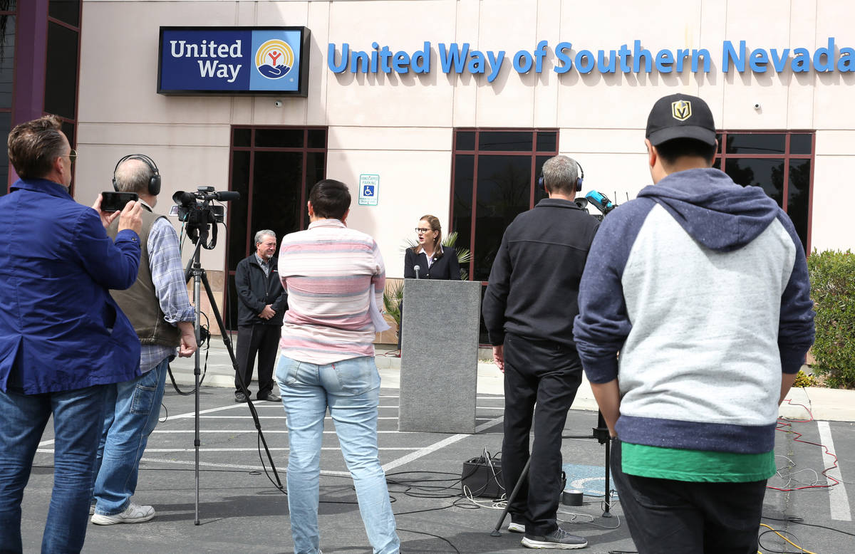 United Way Southern Nevada President and CEO Kyle Rahn, center, speaks as Tony Sanchez, third l ...