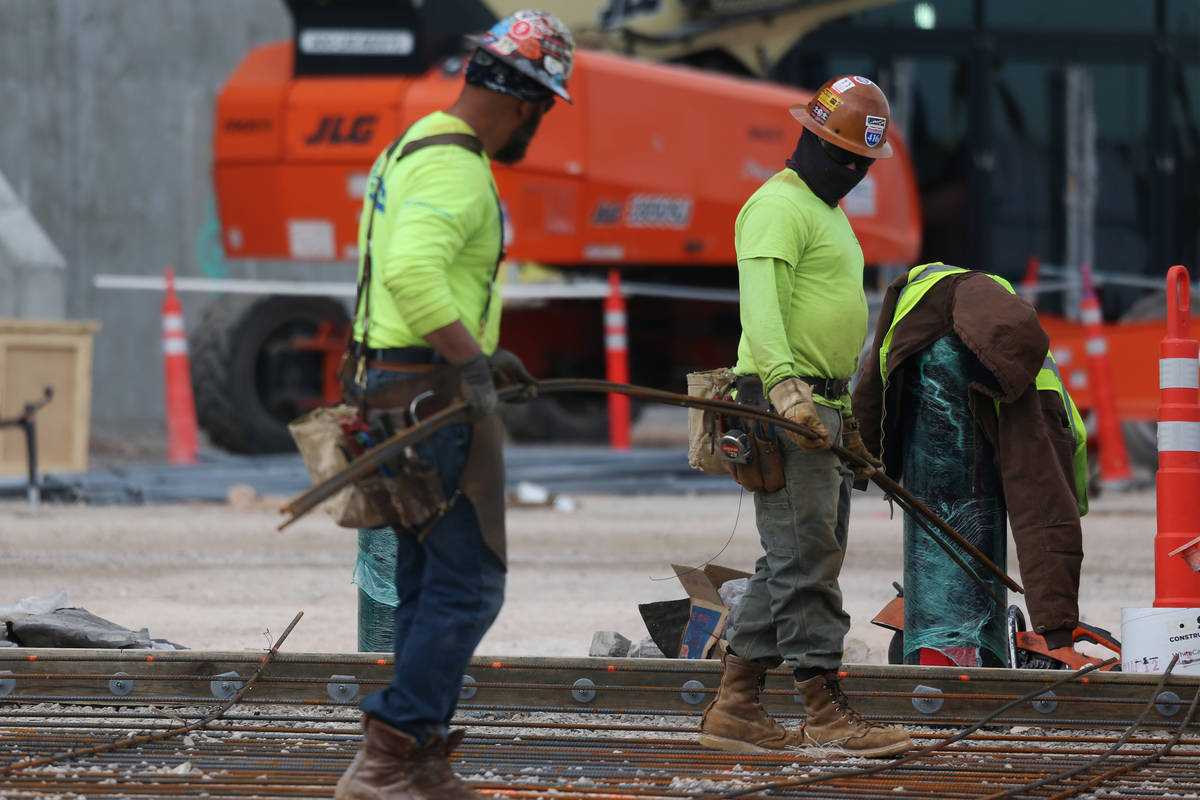 Workers carry rebar steel at the Raiders Allegiant Stadium construction site in Las Vegas, Wedn ...