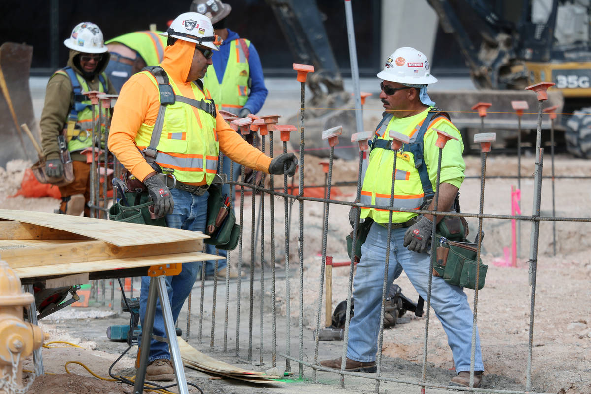 Workers speak to each other at the Raiders Allegiant Stadium construction site in Las Vegas, We ...