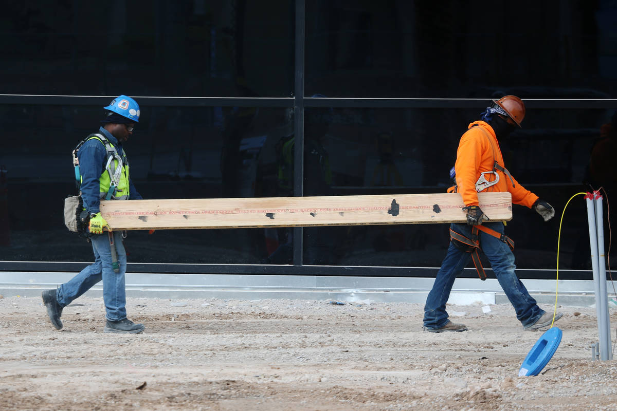 Workers carry a board at the Raiders Allegiant Stadium construction site in Las Vegas, Wednesda ...
