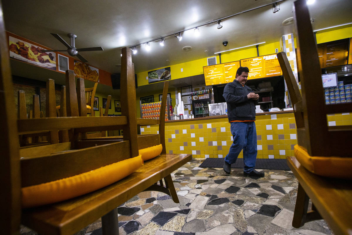 Felix Arellano, owner of Viva Las Arepas, walks through his restaurant as it gets boarded up in ...