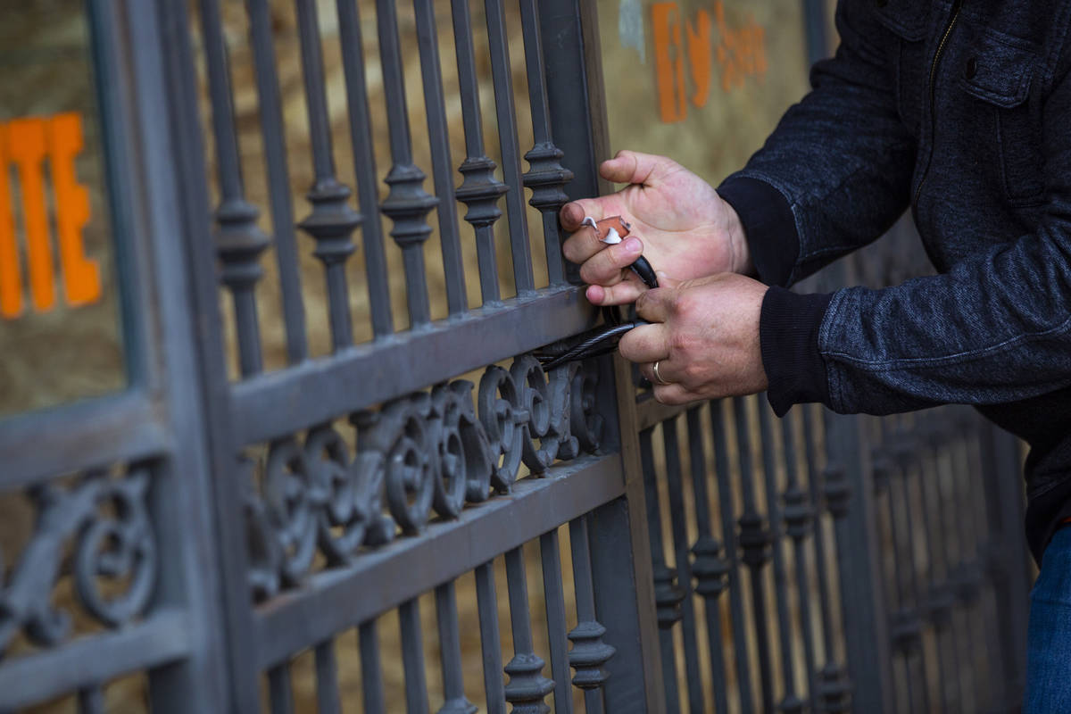 Felix Arellano, owner of Viva Las Arepas, locks the gate to an outdoor eating area as his resta ...