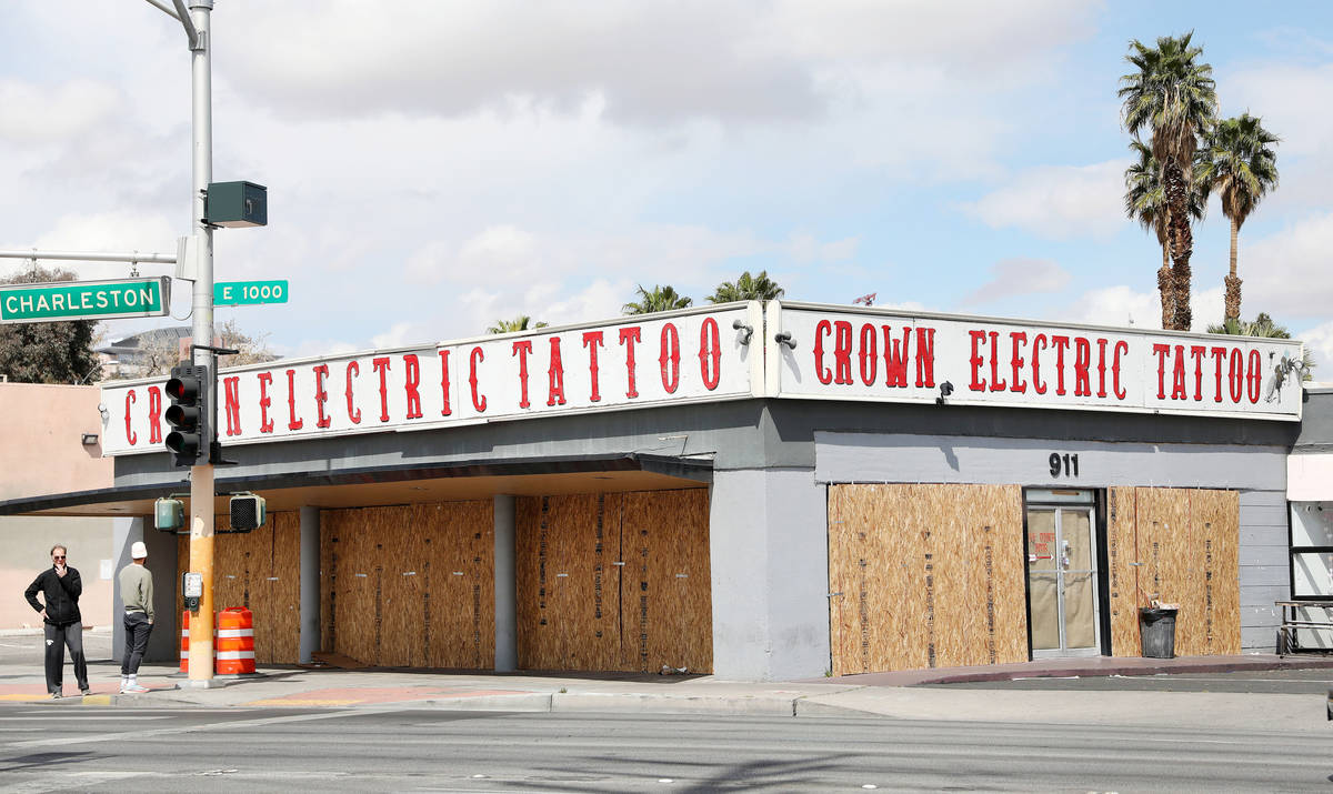 Pedestrians walk pass the recently boarded Crown Electric Tattoo Co. located on 911 East Charle ...