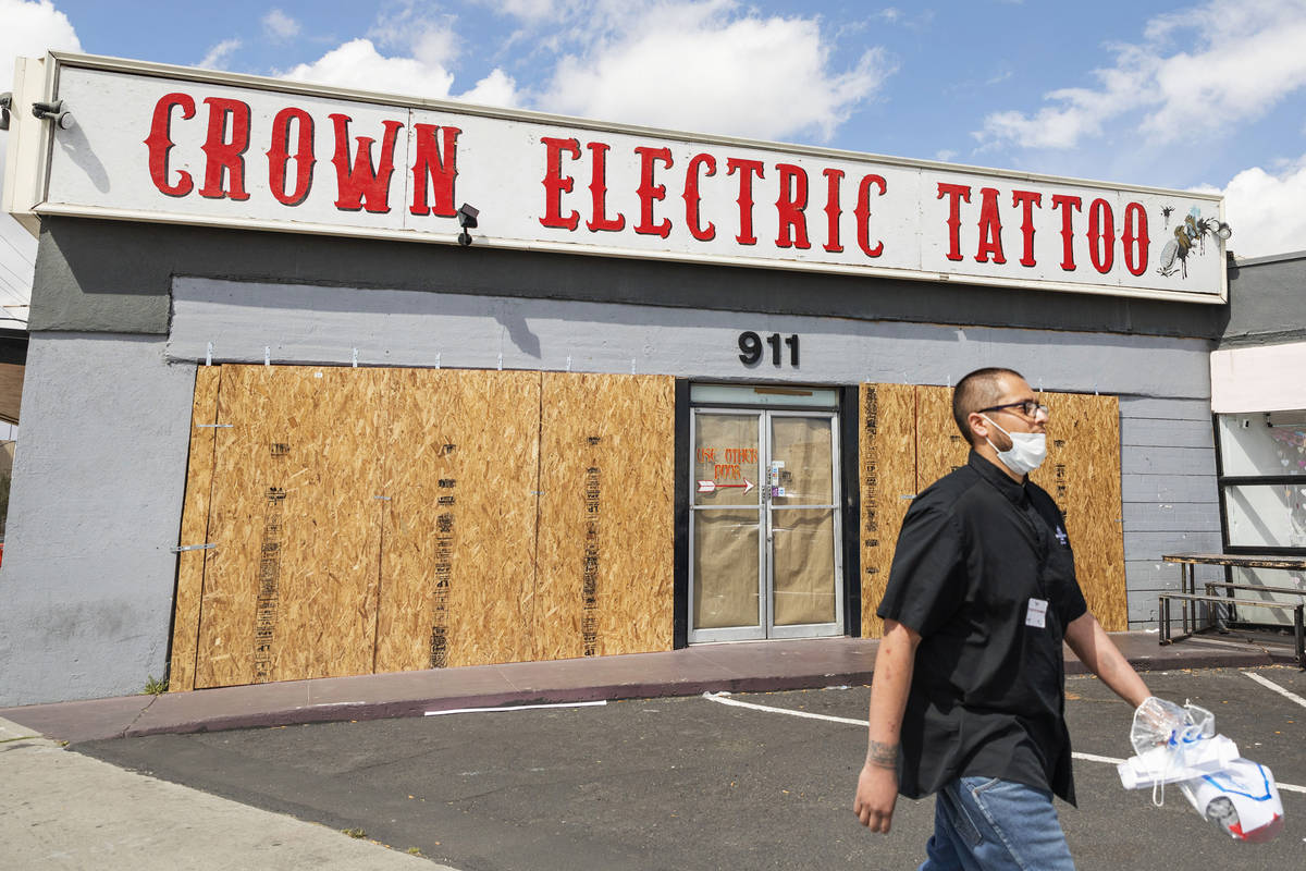 Surgio Aguirre of North Las Vegas walks by the recently boarded Crown Electric Tattoo Co. locat ...