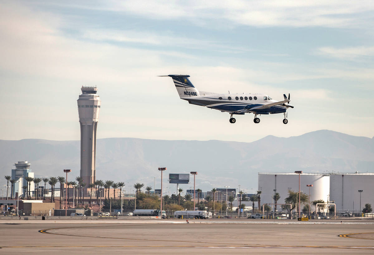 A plane passes by the air traffic control tower as it prepares to land at McCarran Internationa ...
