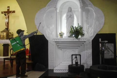 A worker disinfects a Catholic church amid fears of the new coronavirus outbreak in Yogyakarta, ...