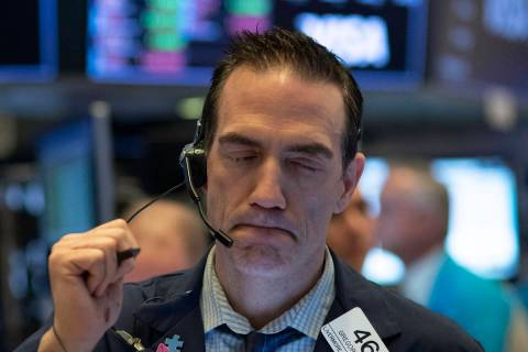 In a Wednesday, March 18, 2020, file photo, trader Gregory Rowe works at the New York Stock Exc ...