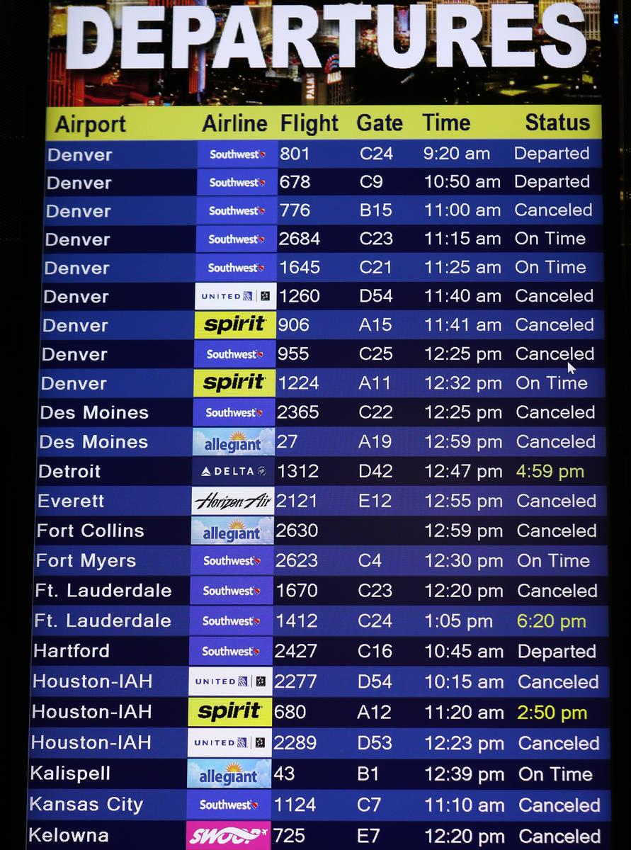 A flight departure information board displays several cancelled flights at Las Vegas McCarran I ...