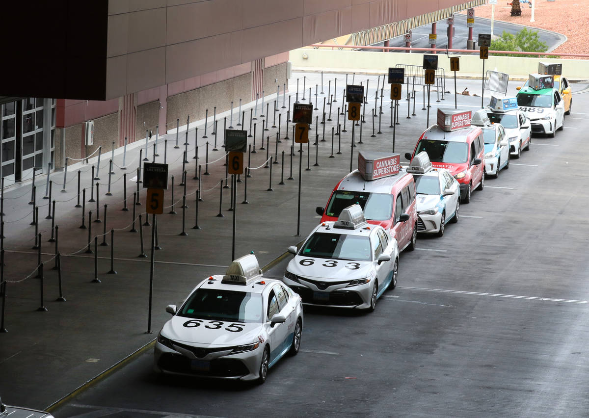 Taxis line up at passengers pick up area at McCarran International Airport on Thursday, March 1 ...