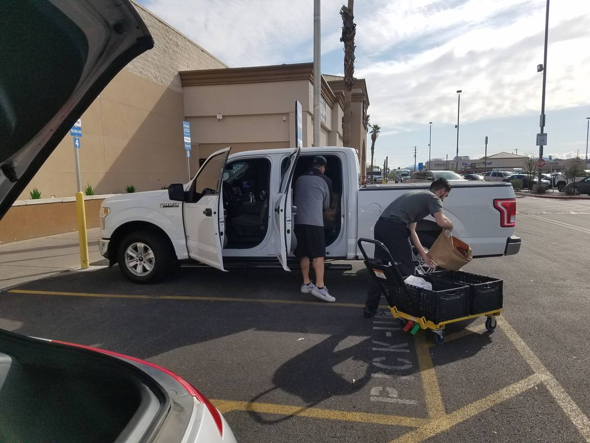 Smith's employee Jagger delivers a pickup order Thursday, March 19, 2020, in Henderson. (Heidi ...
