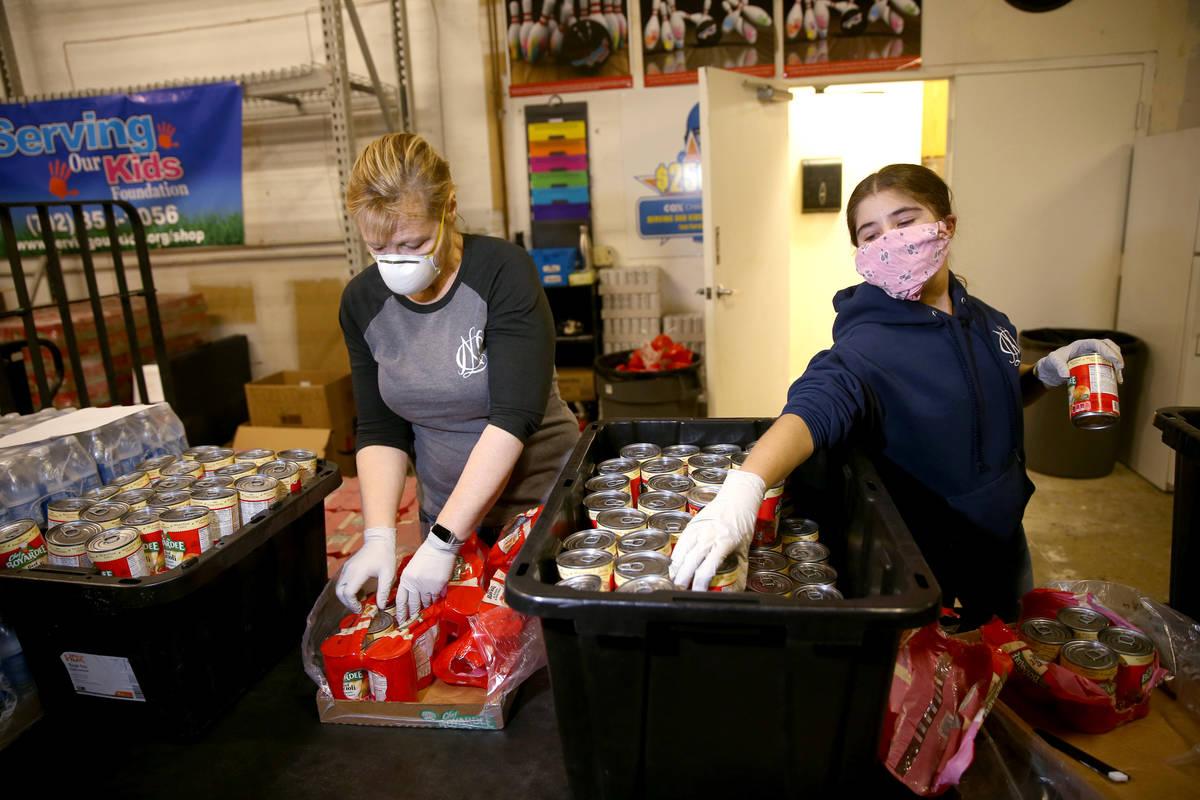 Volunteers Sara Ricciardi and her daughter Grace, 14, of Henderson prepare food for a later bag ...