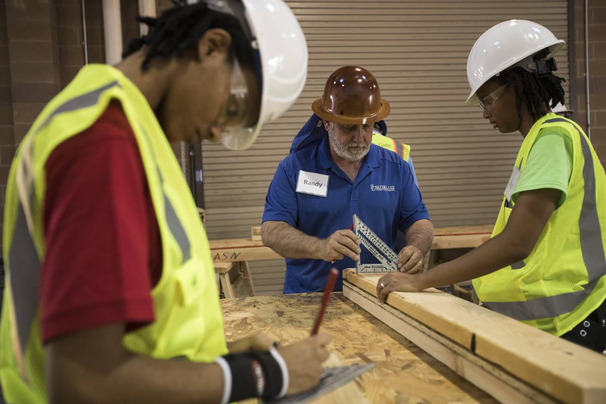 Randy Griebel, center, helps students and sisters Tamira Williams, left, and Alex Coulter, righ ...
