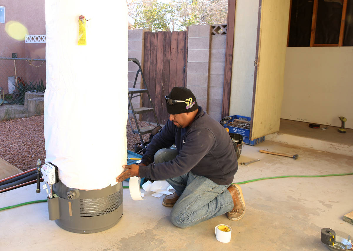 Abraham Gonzalez insulates a water heater outside a Las Vegas home in this Dec. 12, 2017, file ...