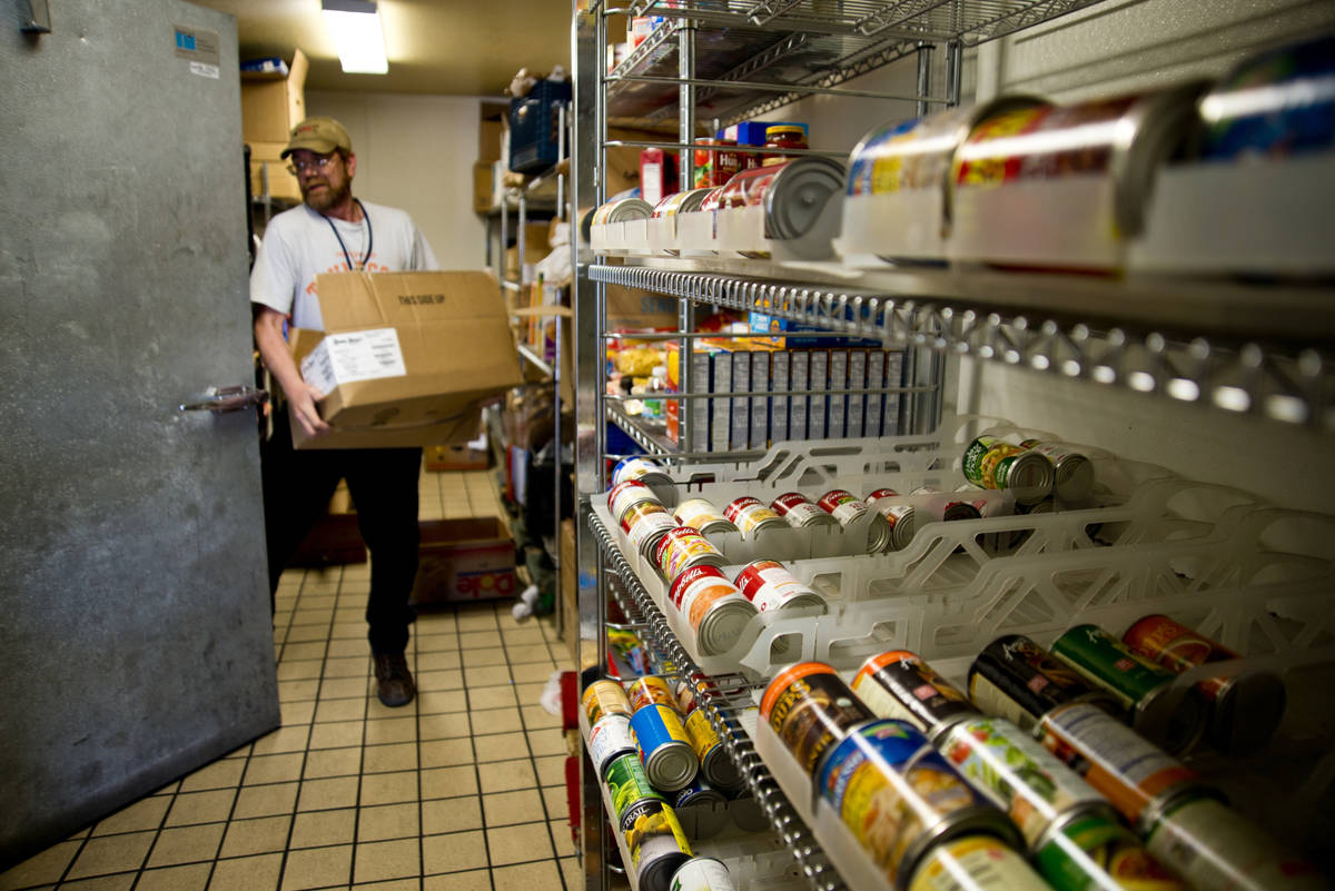 Scott Shepard carries a box of donated food into a large refrigerator at Casa de Luz community ...