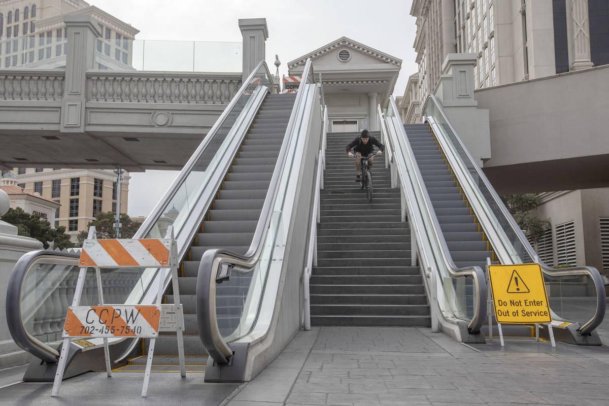 Las Vegan Matt Cremeans bikes down stairs of a pedestrian bridge on the Strip is empty on Wedne ...