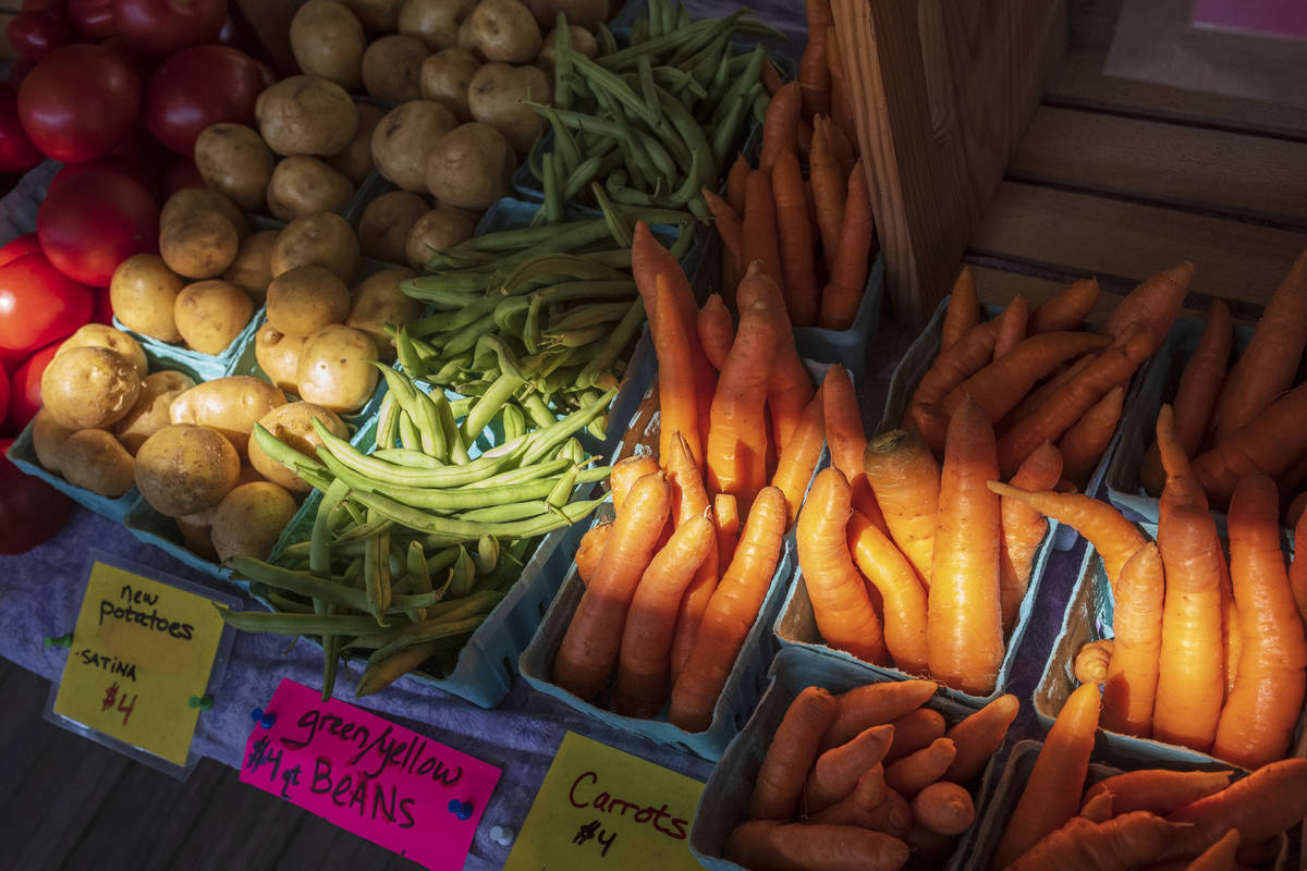 Fresh vegetables, carrots, green beans, potatoes and tomatoes, for sale at a farmers market sta ...