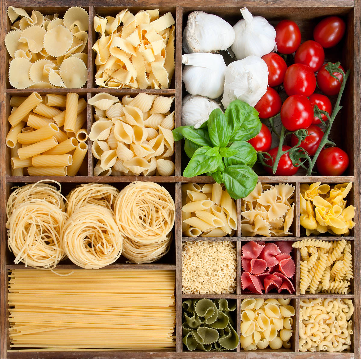 Assorted pastas in wooden box with cooking ingredients