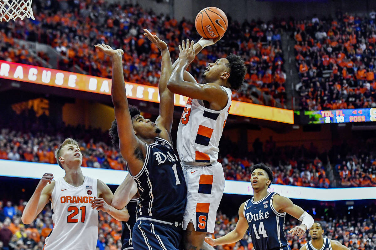 FILE - In this Feb. 1, 2020, file photo, Syracuse forward Elijah Hughes, right, shoots over Duk ...