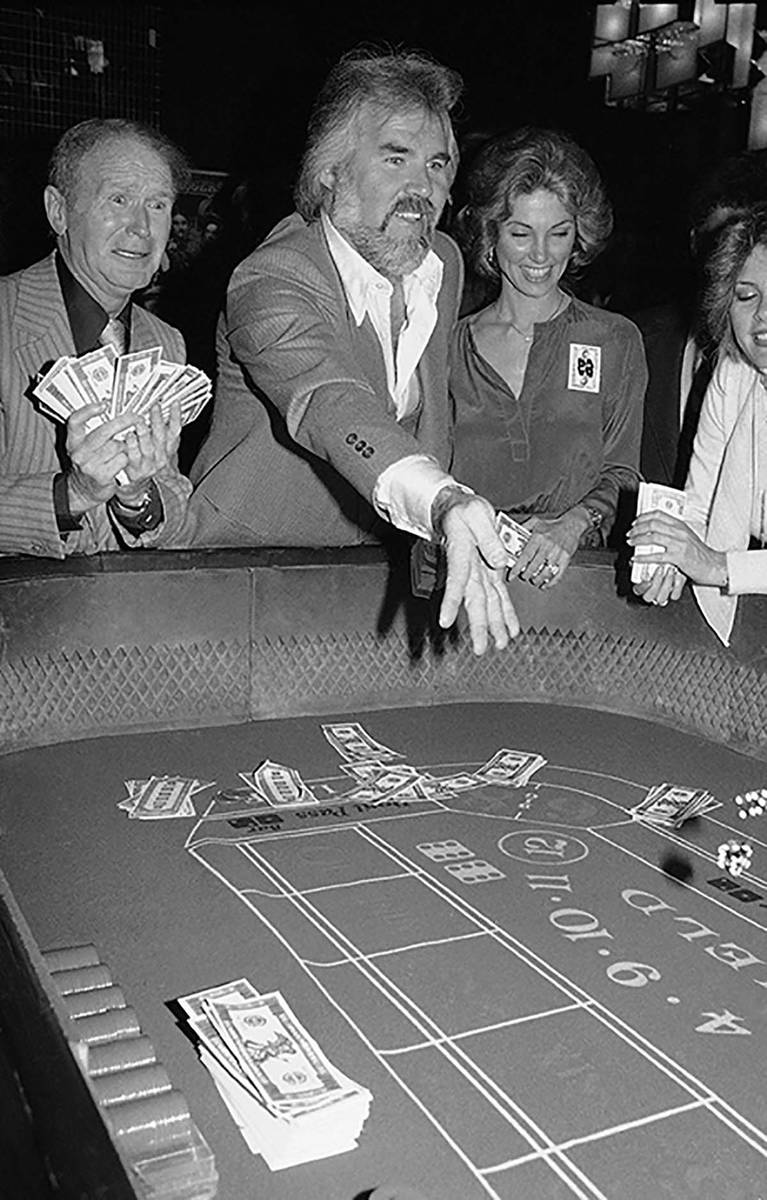 In this March 22, 1979 file photo, Kenny Rogers, center, rolls the dice at Regine's in New Yo ...