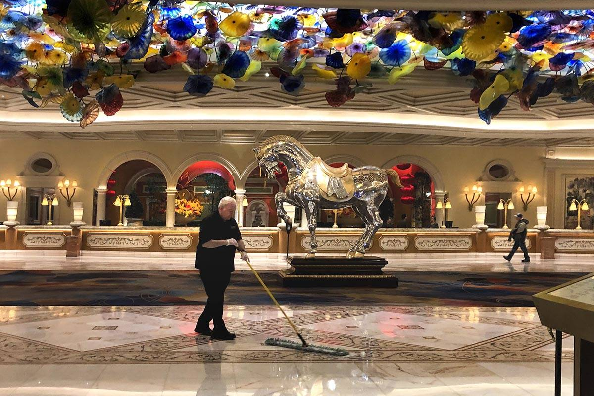 A janitor sweeps up the atrium within the Bellagio as MGM shuts down casino operations at midni ...