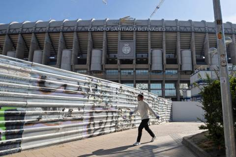 A woman wearing a protective mask walks past Real Madrid's Santiago Bernabeu stadium in Madrid, ...