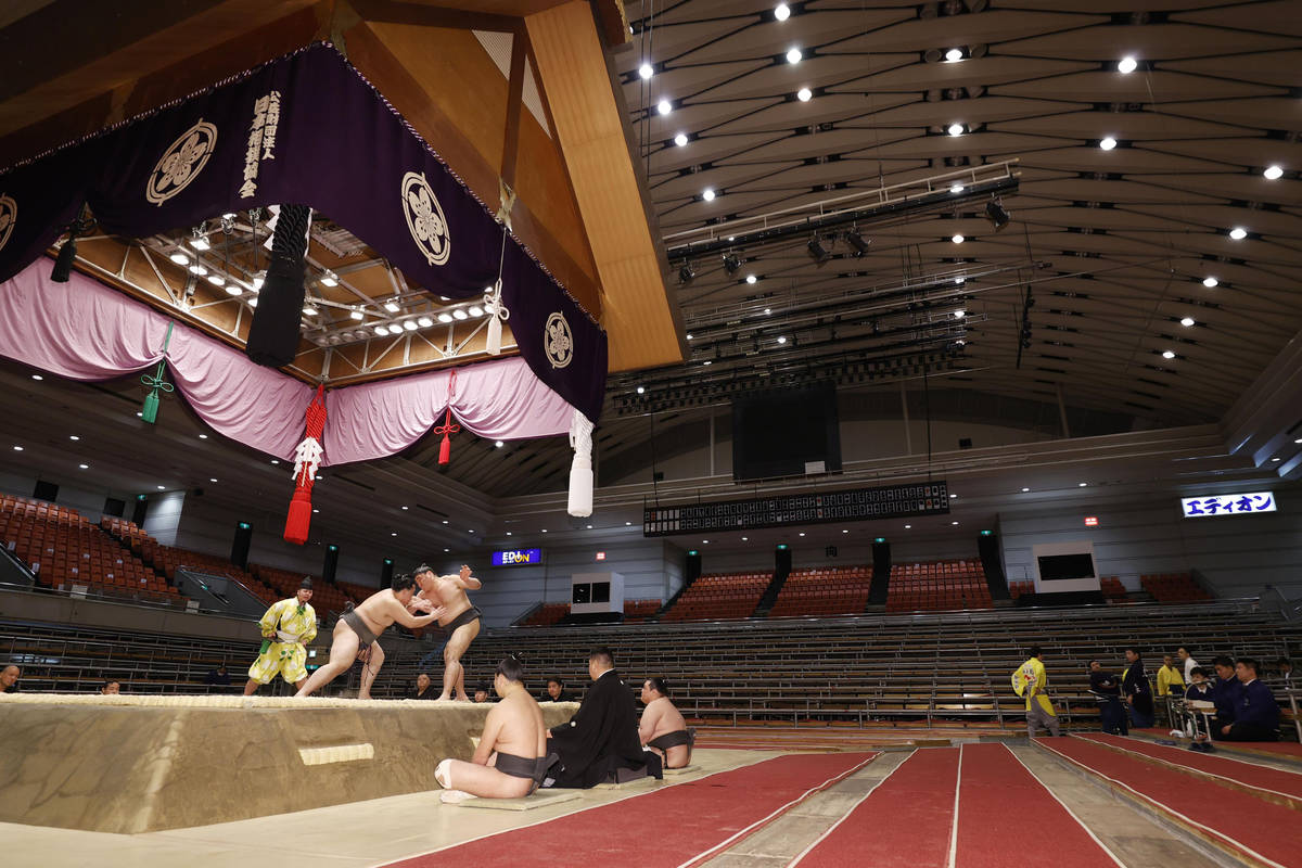 Sumo wrestlers fight on the ring as spectators' seats are empty during the Spring Grand Sumo To ...