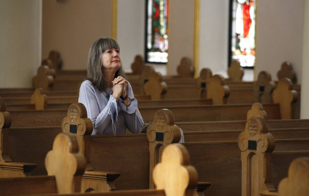 Due to the coronavirus, a parishioner prays during a modest and shortened service at St. Mary's ...