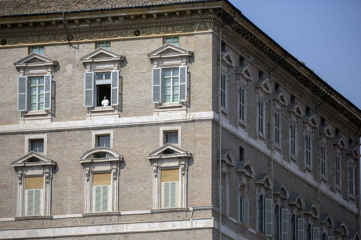 Pope Francis delivers his blessing from the window of his private library overlooking an empty ...