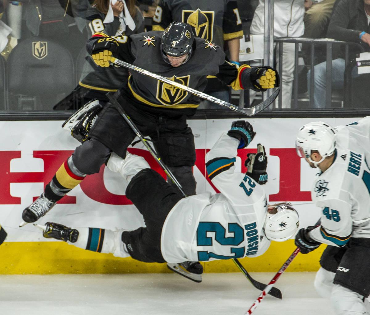 Golden Knights defenseman Brayden McNabb (3) puts a big hit on San Jose Sharks right wing Joona ...
