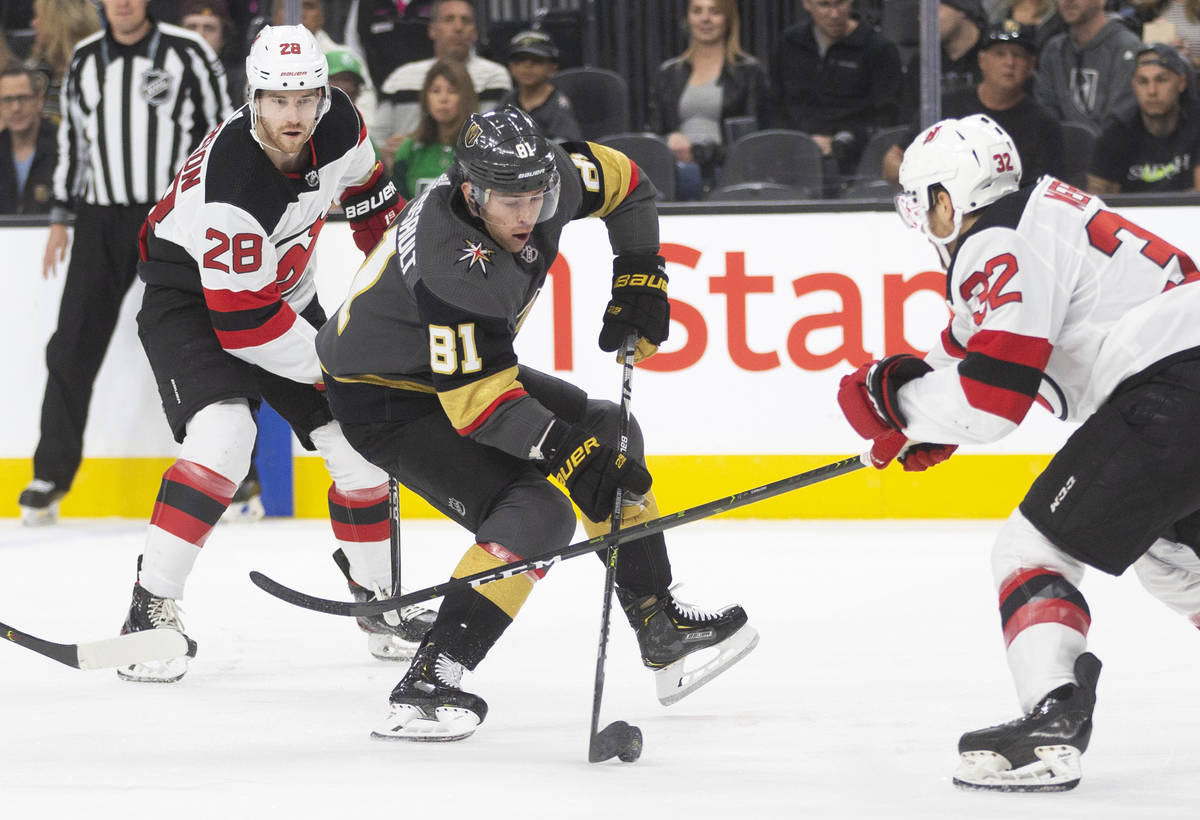 Vegas Golden Knights center Jonathan Marchessault (81) tries to skate around New Jersey Devils ...