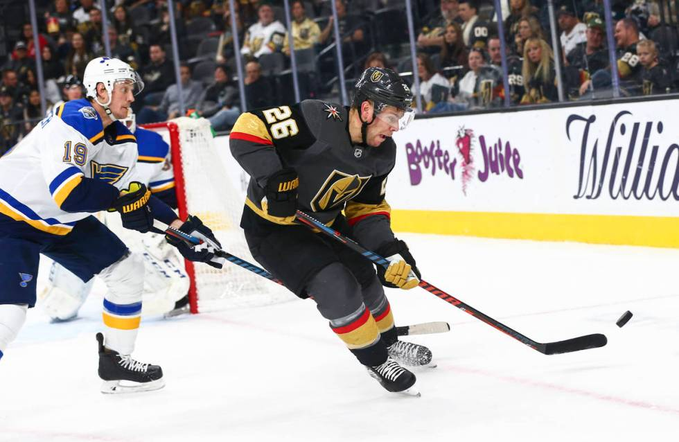 Golden Knights' Paul Stastny (26) eyes the puck in front of St. Louis Blues' Jay Bouwmeester (1 ...