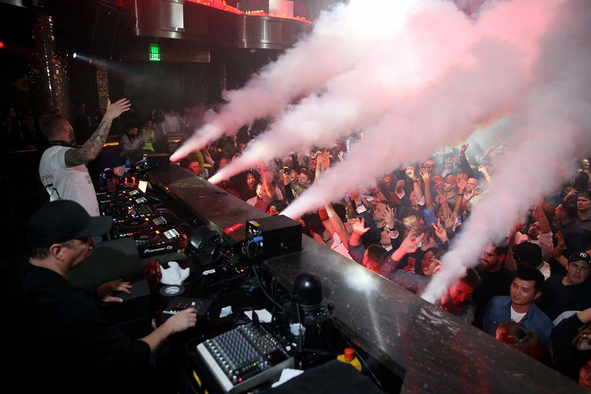 Conventioneers and clubgoers dance to DJ Mark Eteson, upper left, during the CES 2020 official ...