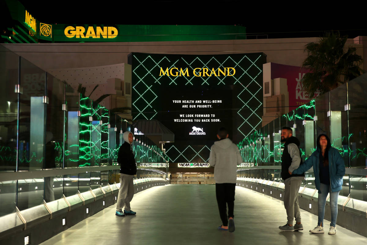 Visitors walk on the pedestrian bridge towards the MGM Grand as non-essential business closures ...