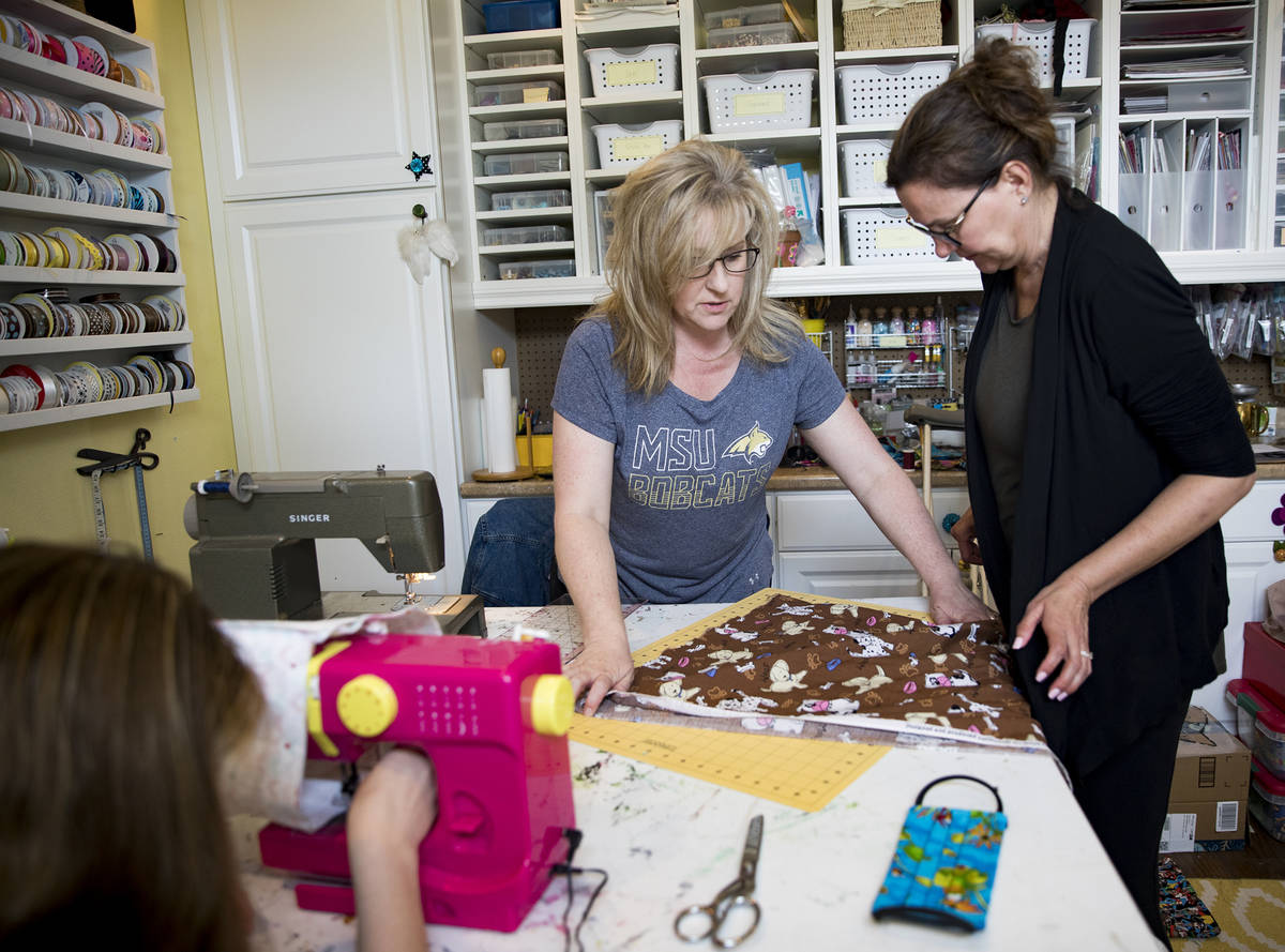 Anissa Gustafson, center, shows her friend Terri Yannone, right, how to cut fabric for masks at ...