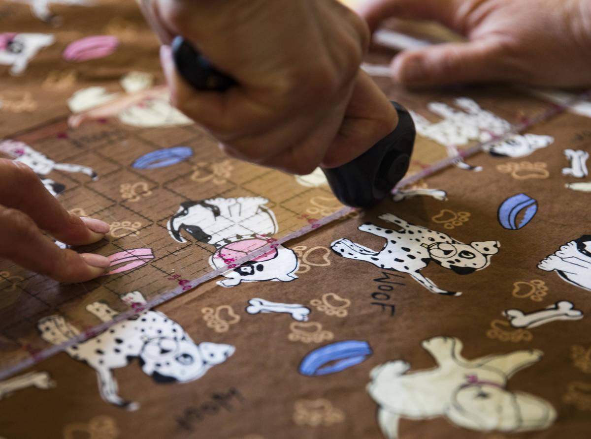 Terri Yannone cuts fabric at her friend Anissa Gustafsonͳ home in Las Vegas, Sunday, Marc ...
