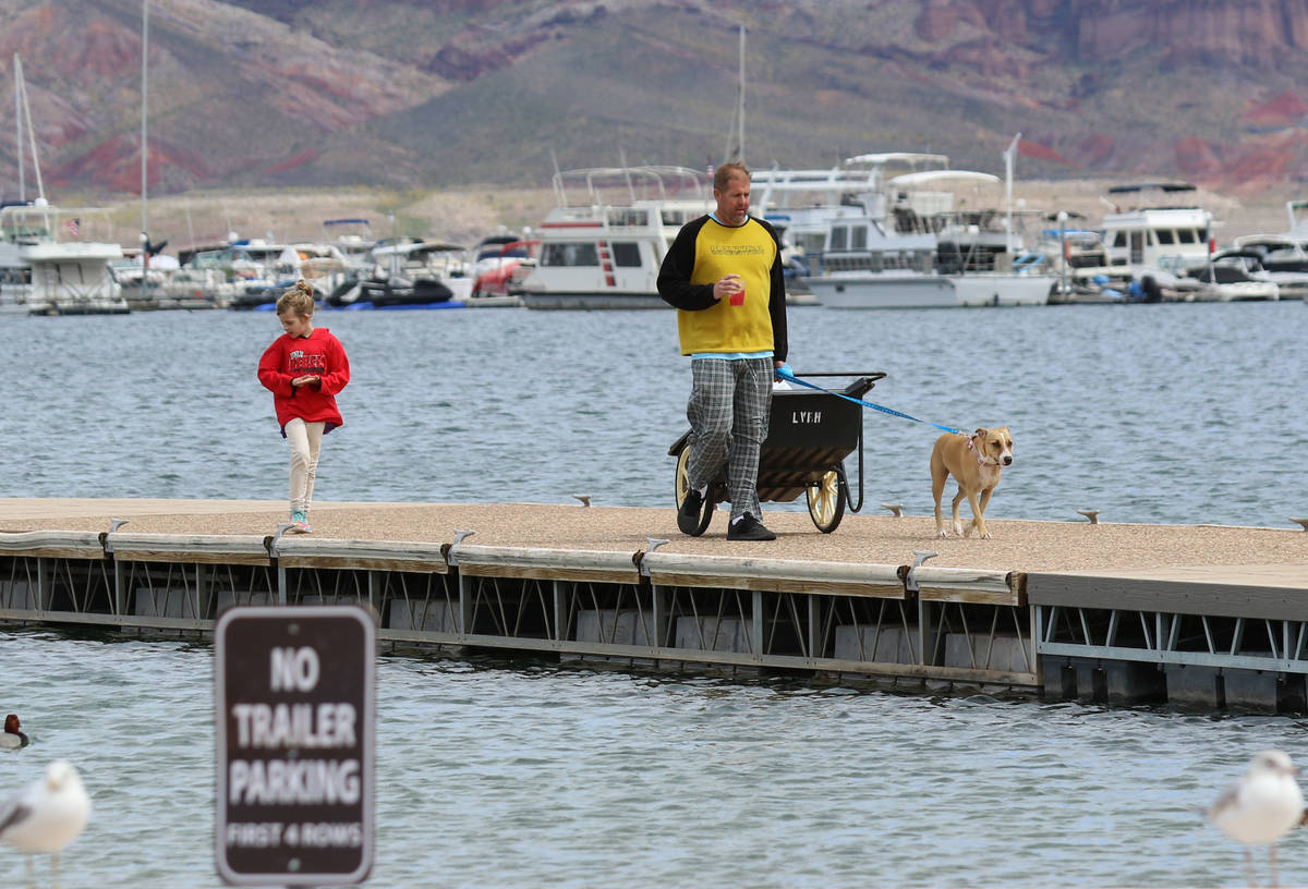 Kurt DeWinter of Henderson pulls his belongings that were retrieved from his boat as his daught ...