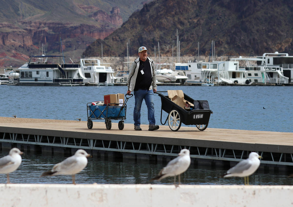 Richard Keeley of Henderson transports his belongings that were retrieved from his boat in cart ...