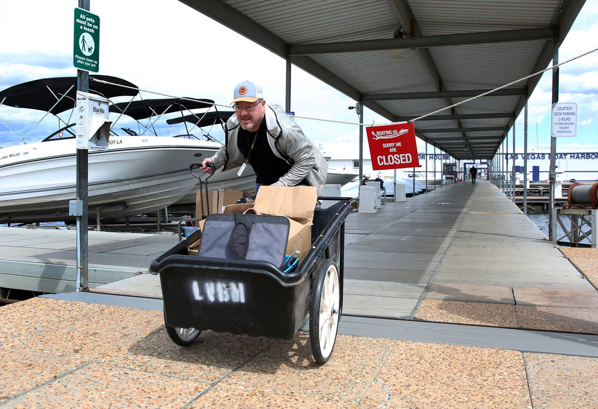Richard Keeley of Henderson pushes his belongings that were retrieved from his boat at Lake Las ...