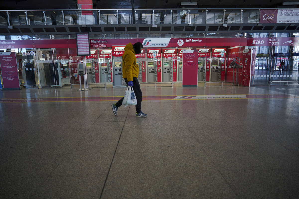 A person walks past ticket machines in an almost empty Termini main train station, in Rome, Mon ...
