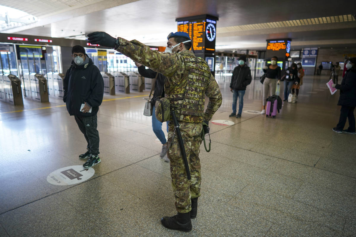 A soldier gives indications to passengers as they line up to have their travel documents checke ...