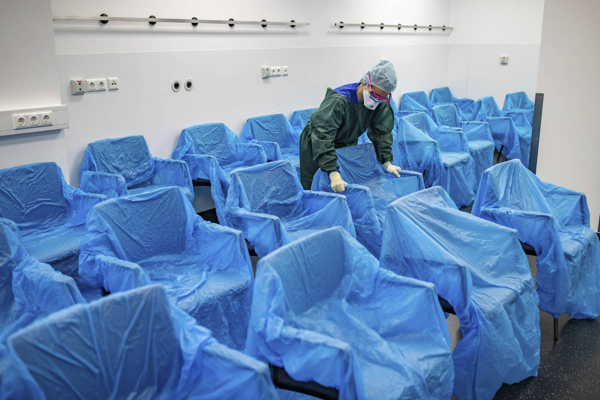 A nurse assembles plastic-wrapped chairs in a waiting area in the central emergency room of the ...