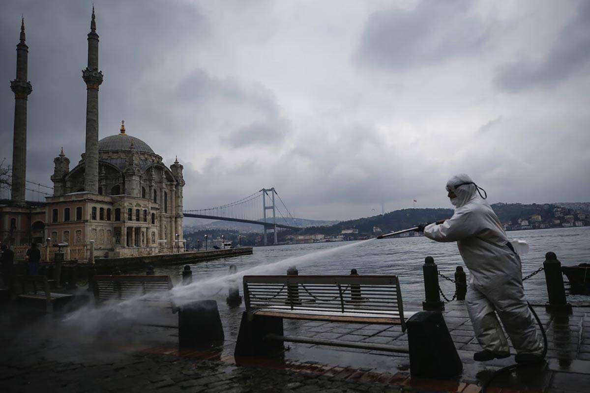 A municipality worker wearing a protective suit sprays water, backdropped by the Ottoman-era Me ...