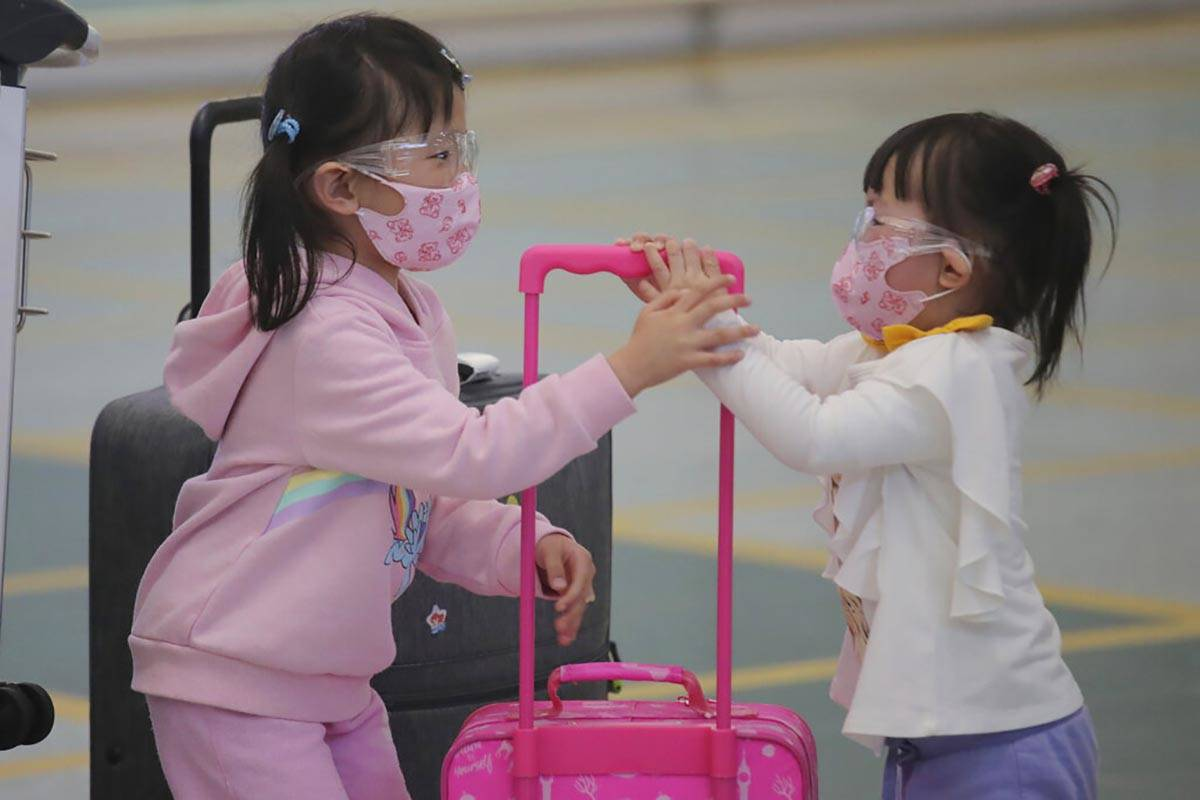 Young passengers wear face masks to protect against the coronavirus as they arrive at the Hong ...