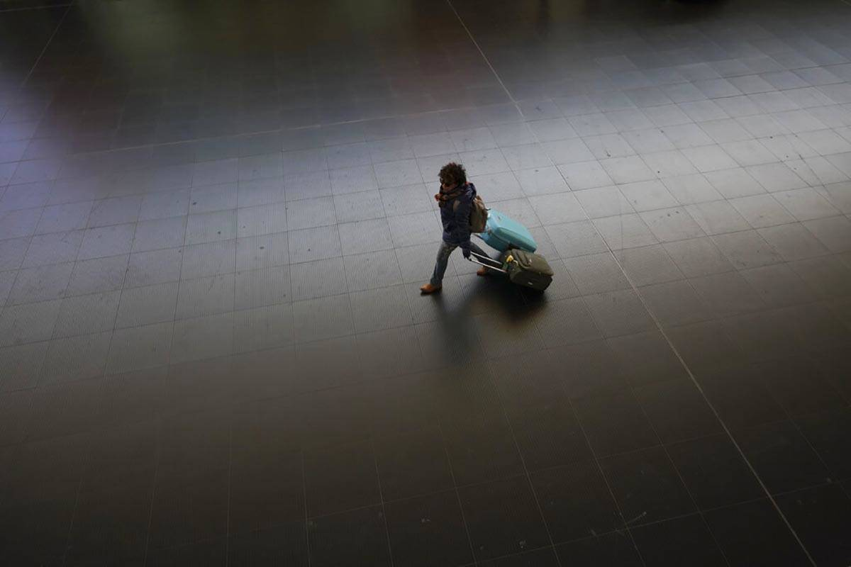 A passenger carries her luggage through an almost empty Termini main train station, in Rome, Mo ...