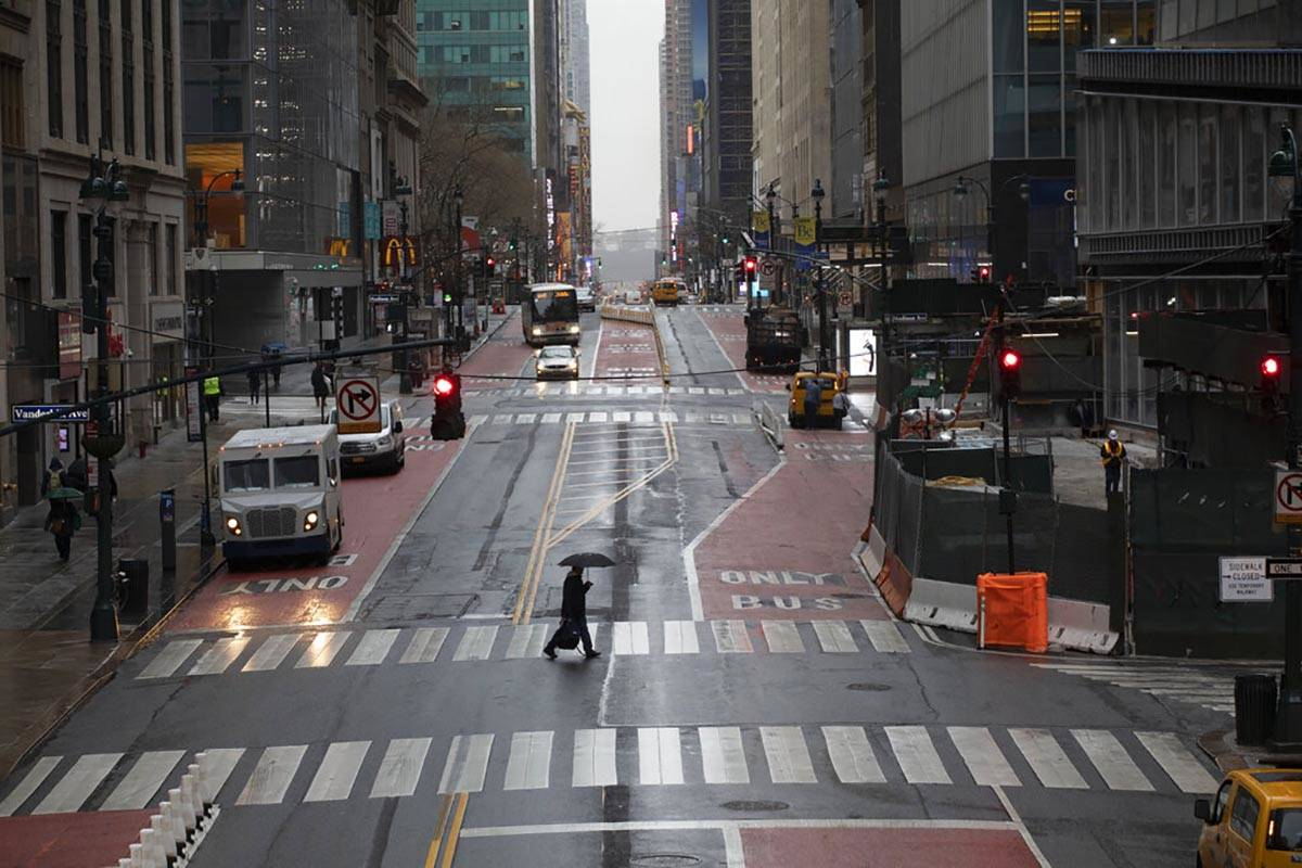 A commuter crosses 42nd Street in front of Grand Central Terminal during morning rush hour, Mon ...