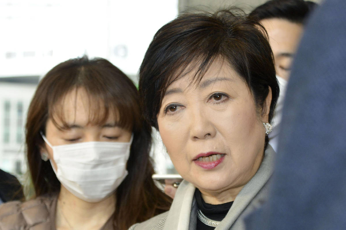 Tokyo Gov. Yuriko Koike, right, answers a reporter's question about the latest policy of Intern ...
