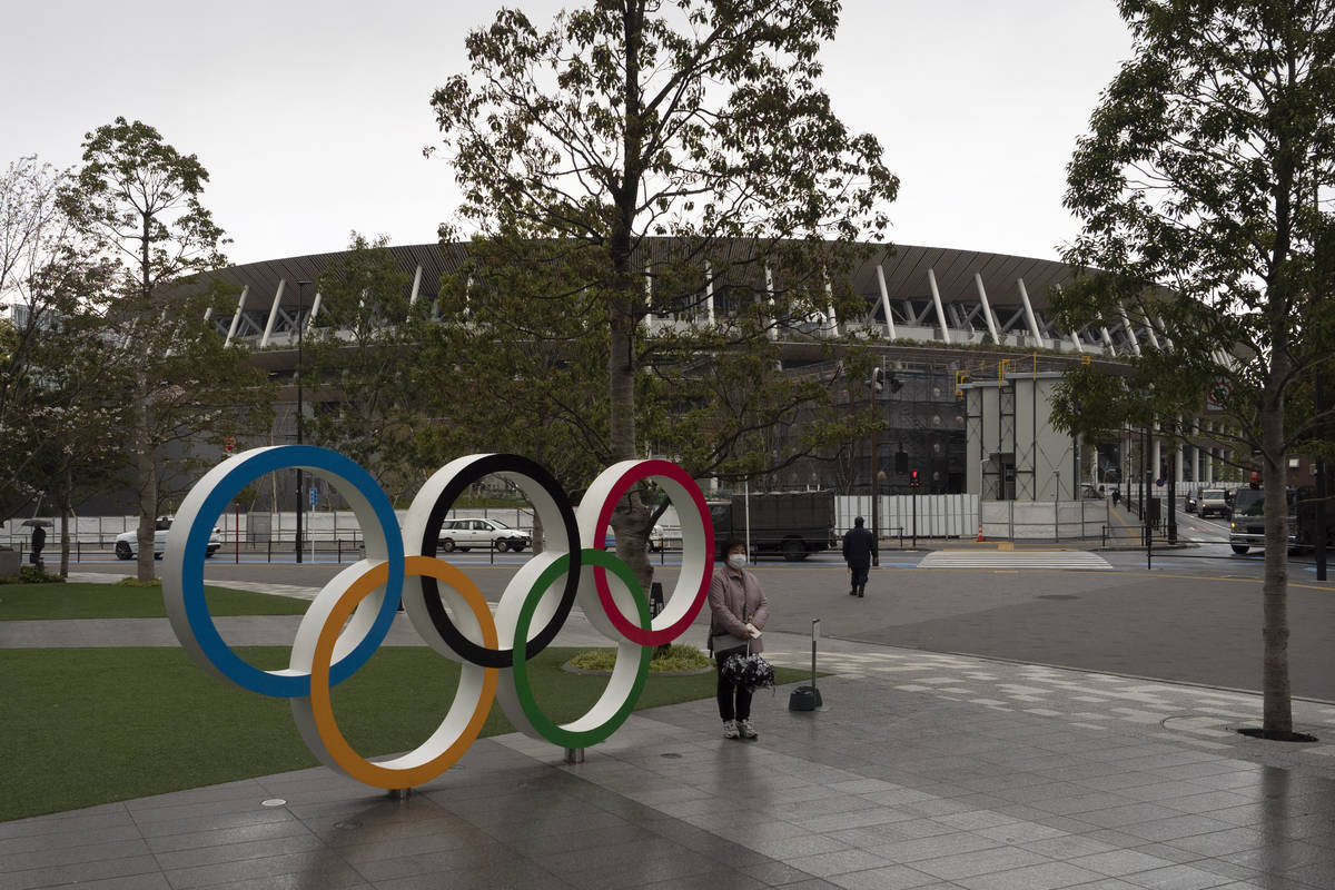 A woman pauses for photos next to the Olympic rings near the New National Stadium in Tokyo, Mon ...