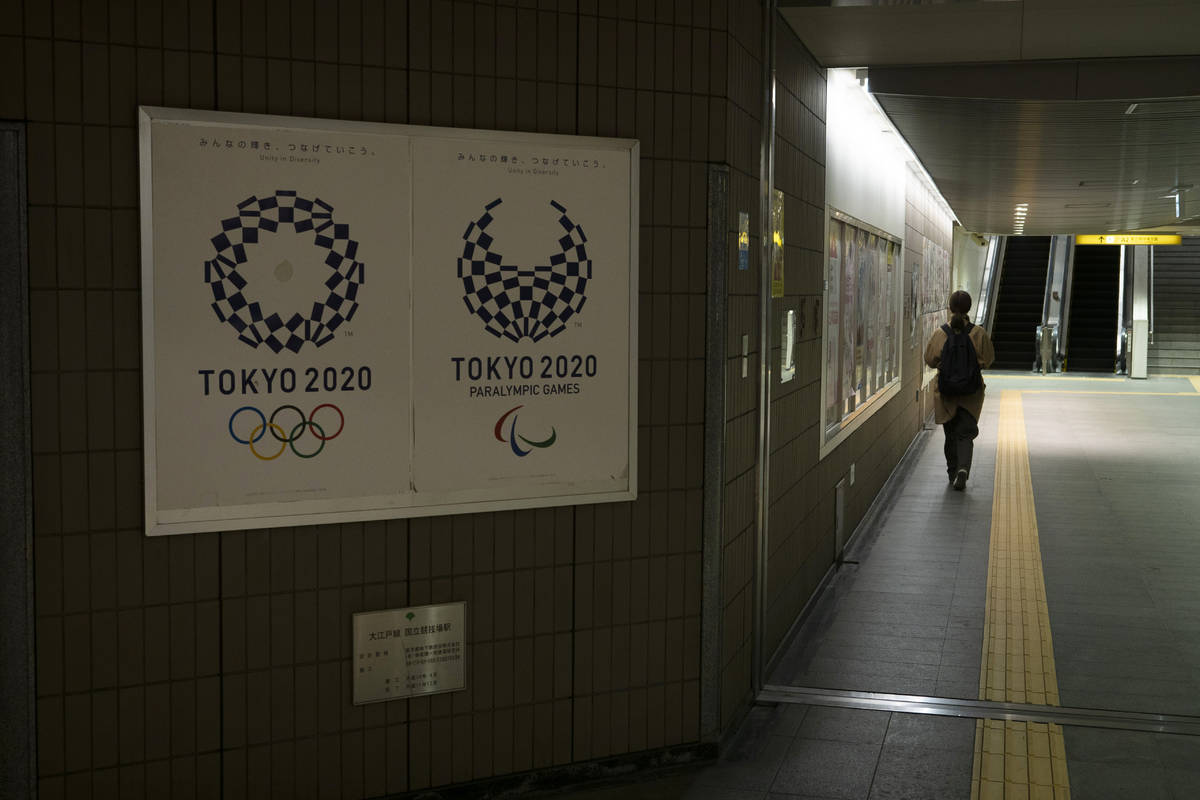 A commuter leaves a train station adorned with posters promoting the Tokyo 2020 Olympics in Tok ...