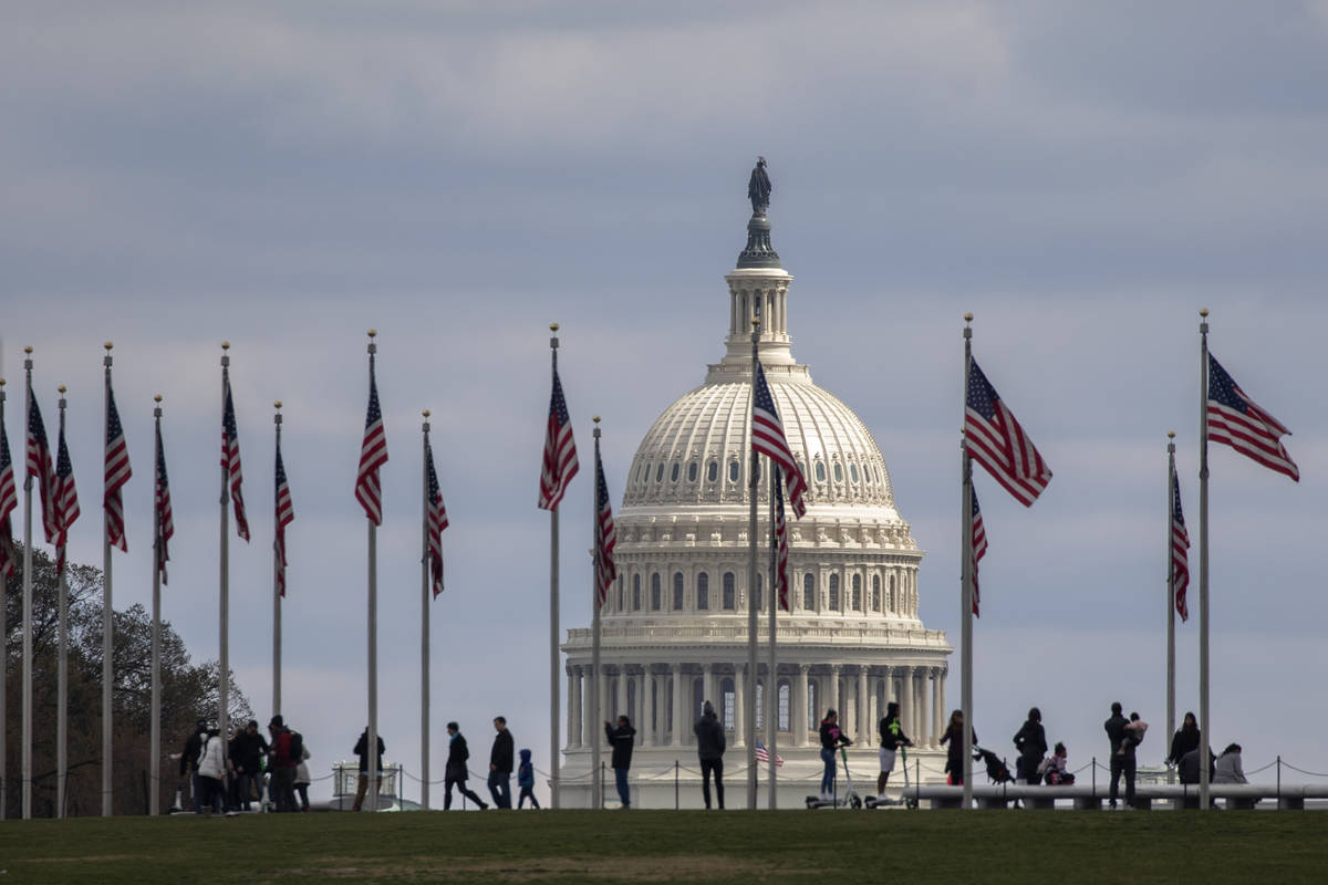 People walk among U.S. flags with the U.S. Capitol in the background, Sunday, March 15, 2020, i ...